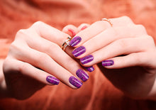 Image of manicured hands wearing nail wraps nail stickers in Purple Shatter design