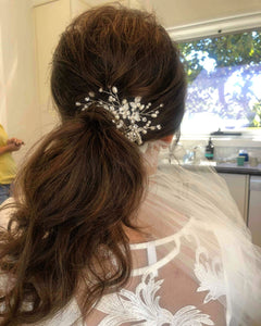 Bride from behind with thick low ponytail achieved with clip in hair extensions and wearing hair accessories