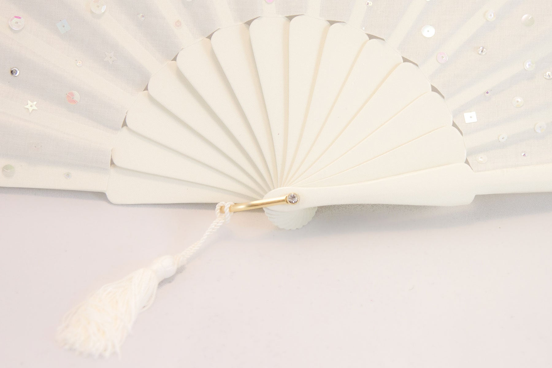 Handmade fan adorned with hand sewn sequins on a cream painted Danta wood frame close up