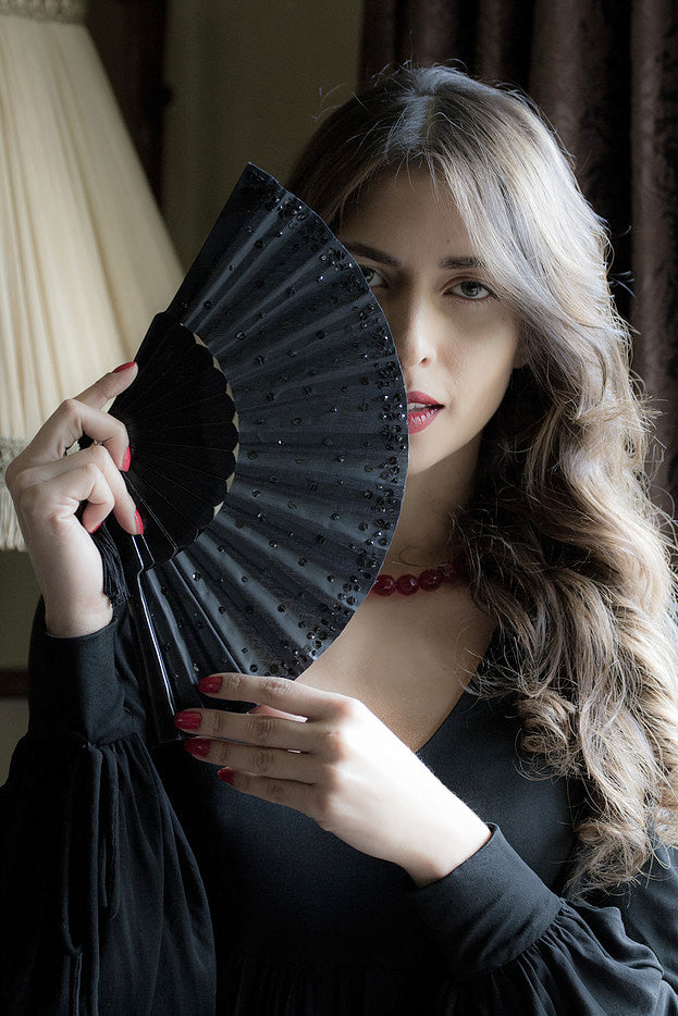 Model holding Black Paris fan with hand sewn sequins