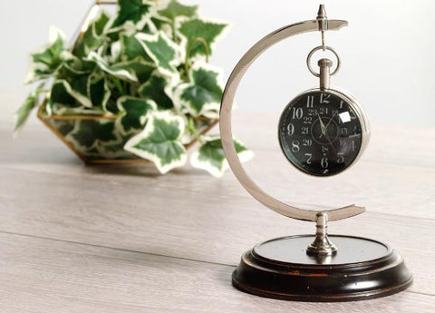 Eye of Time clock on stand on table