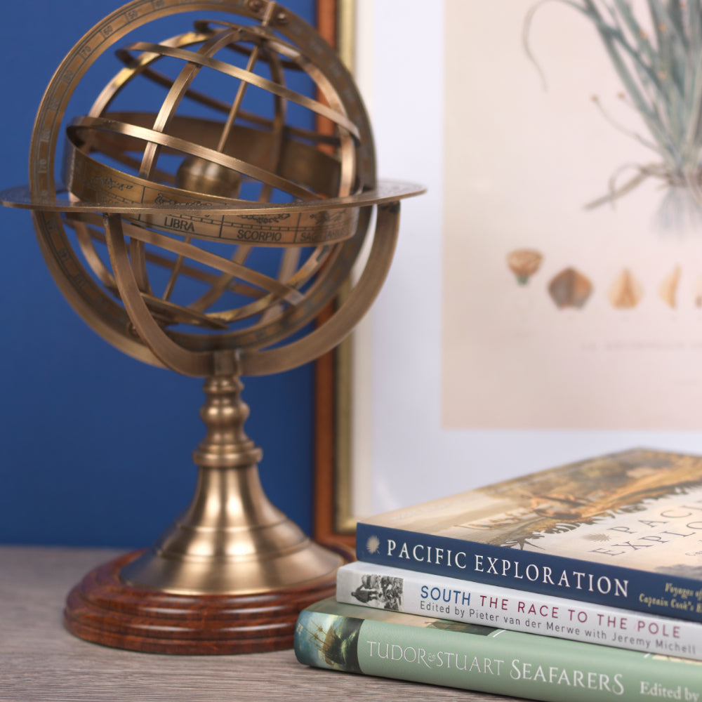 Large armillary sphere next to stack of books