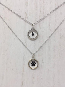 Close up picture of two sterling silver necklaces. The top necklace has a black cat pendant while the second necklace has a black paw print pendant