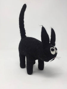 Picture of a black felt cat standing on a white surface
