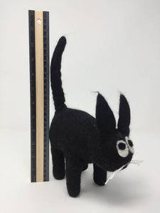 Picture of a black felt cat toy standing on a white surface with a ruler behind it