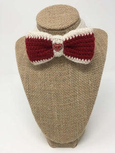 Red and white hand-knitted bow tie pet collar around a tan brown bust