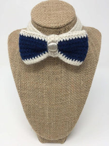 Blue and ivory hand-knitted pet bow tie on the neck of a tan brown bust