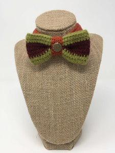 Hand-knitted green, burgandy, and orange pet bow tie on a tan brown bust