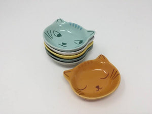 Picture of five mini cat face bowls stacked on top of each other with another orange mini bowl next to the stack