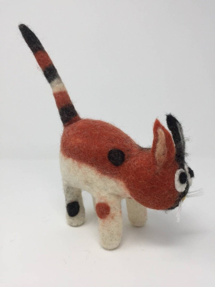 Orange, white, and black felt cat toy standing on a white surface showcasing the side of the cat