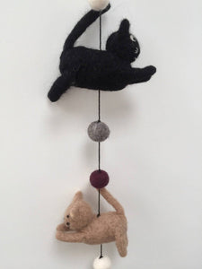 Picture of a black felt cat and a brown felt cat on a string with felt balls between them