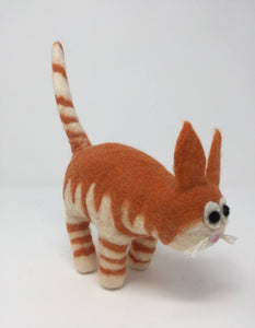 Picture of a striped orange felt cat standing on an all white surface