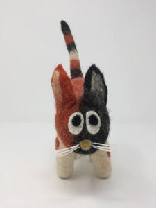 Orange, white, and black felt cat toy standing on a white surface facing front