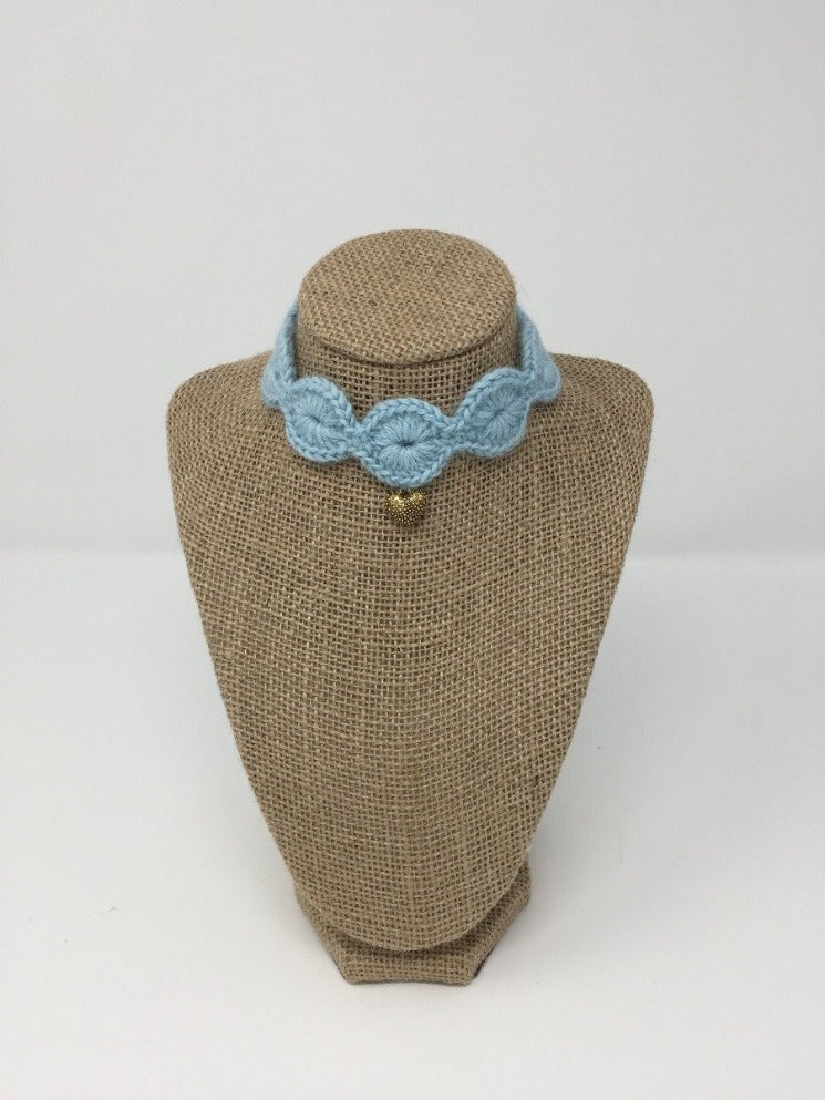 Picture of a light blue pet collar with a gold colored pendant around a tan brown bust