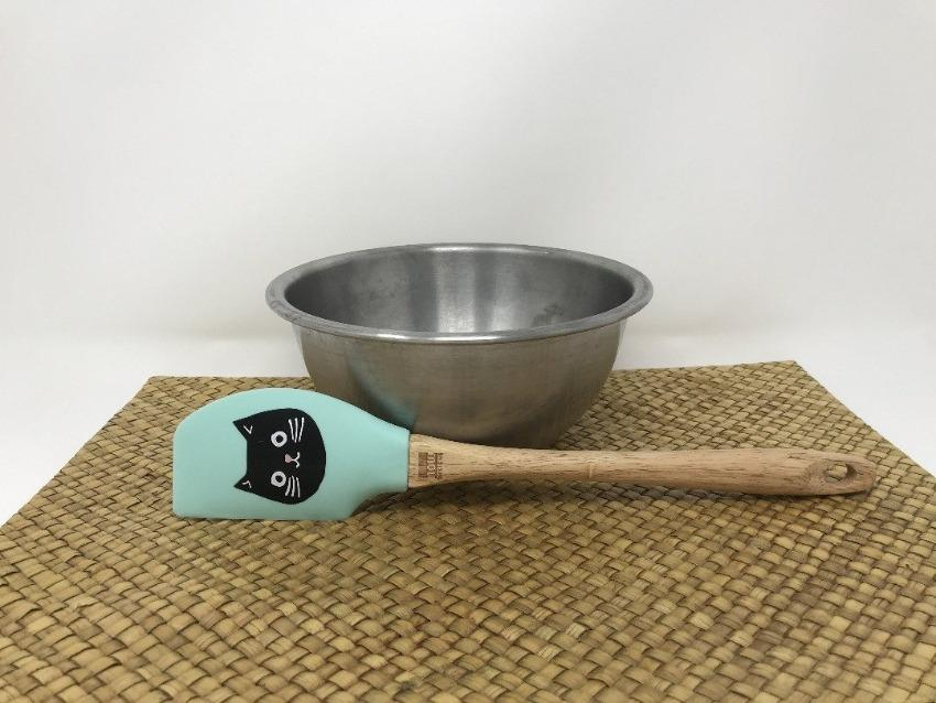 Wooden handled spatula with a turquoise green head featuring a black cat on it in front a silver bowl