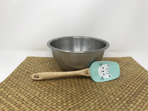 Wooden handled spatula with a turquoise green head featuring a white cat on it in front a silver bowl behind it