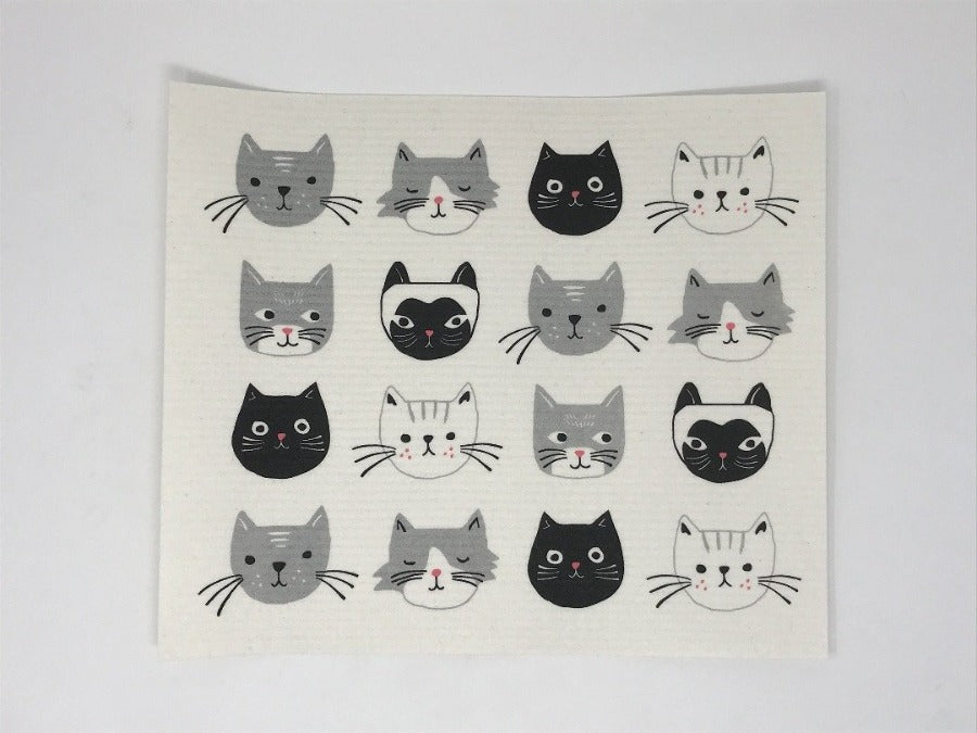 White dish rack mat featuring white, black, and grey cats, laying flat on a white surface