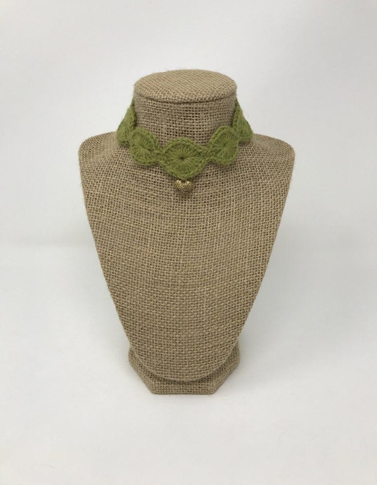 Picture of an olive green hand-knitted pet collar with a gold colored charm around a tan brown bust