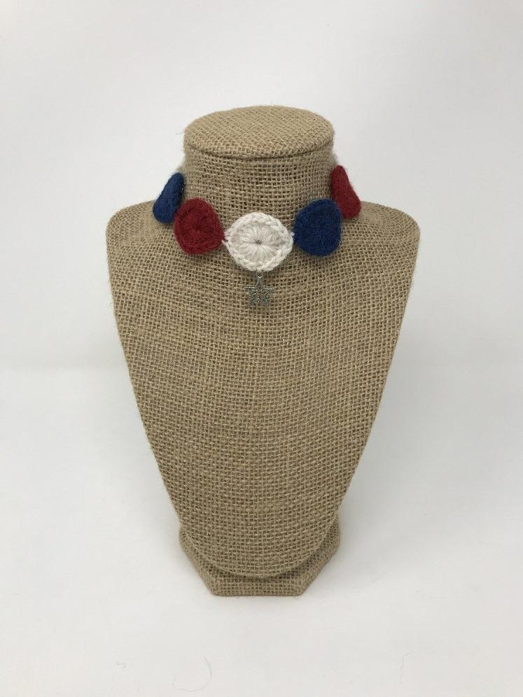 Red, white, and blue hand-knitted pet collar with silver star of David charm around a tan brown bust