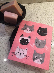 Pink sponge dish rack mats with black, grey, and black cat on a white kitchen countertop surface