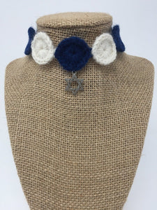 Close up picture of a Blue and ivory hand-knitted pet collar with star of David star around a tan brown bust
