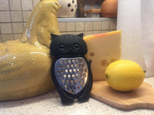 Picture of a black cat-themed kitchen grater with stainless steel front with a lemon to the right of it, a block of cheese to the back of it, and a porcelain chicken sculpture to the left, standing on a white quartz surface