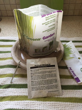 A picture of an open bag of pet greens self-grow kit standing on a circular plant dish