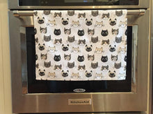 Load image into Gallery viewer, White cat-themed kitchen dish towel featuring numerous cats on it hanging from an oven handle bar