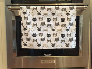 White cat-themed kitchen dish towel featuring numerous cats on it hanging from an oven handle bar
