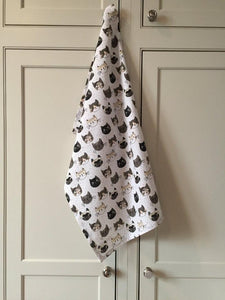 White cat-themed kitchen towel hanging from a kitchen cupboard handle