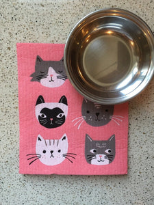 Pink sponge dish rack mats with black, grey, and black cat on it. There is a silver bowl on top of the dish towel