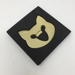 Picture of a gold colored cat face bottle opener inside of black casing laying flat on an all white surface