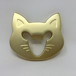 Picture of a gold colored cat face bottle opener laying flat on an all white surface