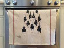 Off-white cat-themed kitchen towel with black cats on them hanging from an oven handle bar