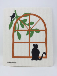 White cat-themed sponge cloth dish rack towel with a black cat looking up at a black bird