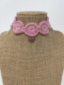 Picture of a Mauve pink hand-knitted Alpaca pet collar with gold colored pendant around a tan brown bust