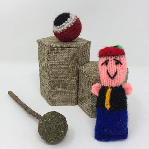 Picture of a pink, blue and red hand-knitted cat toy, and a red, black, and white hand-knitted ball behind it