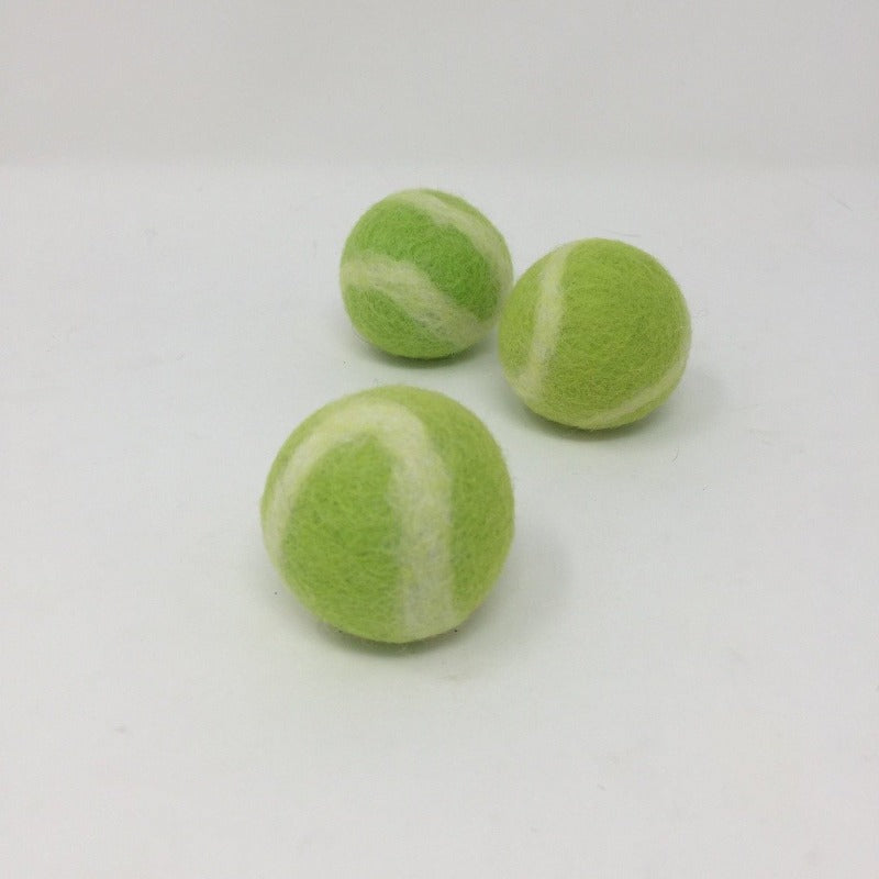 Picture of three green and white tennis balls for pets on a white background