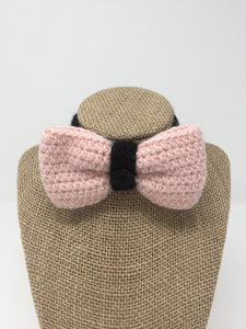 Pink and black Hand Crochet Alpaca Wool Pet Bow Tie around a tan brown bust