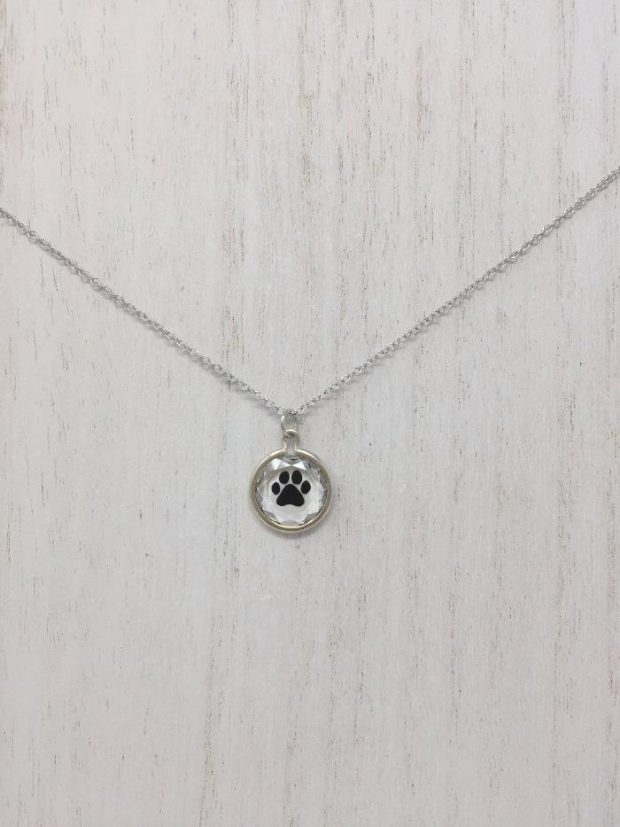 Picture of a sterling silver necklace with a circular pendant and a black paw inside of the pendant