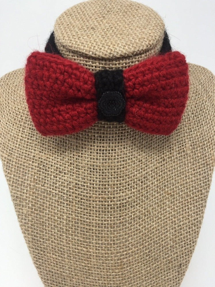 Red and black hand-knitted pet bow tie collar around a tan brown bust