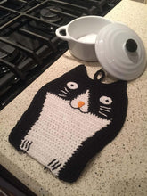 Picture of a black and white hand-knitted cat-themed drink coaster laying flat on a white kitchen surface