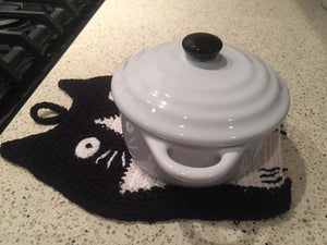 Picture of a black and white hand-knitted cat-themed drink coaster with a small white sugar bowl on it