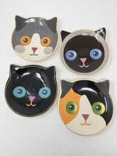 Four cat-themed dessert dishes laying flat on a white surface facing up