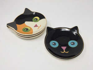 Two cat-themed dessert dishes, one black cat and one brown, white, and black cat laying flat on a white surface
