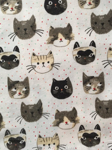 Close up picture of a white cat-themed kitchen towel featuring numerous cats on it