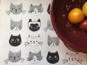 White cat-themed dish rack mat, featuring white, black, and grey cats. on a white kitchen surface. there are some vegetables in a red bowl laying on the towel