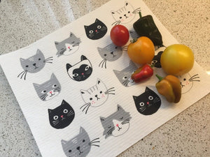 White cat-themed dish rack mat, featuring white, black, and grey cats. on a white kitchen surface. there are some vegetables laying on the towel
