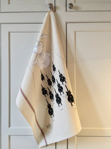 Off-white cat-themed kitchen towel with black cats on them hanging from a cupboard handle