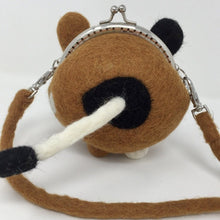 close up picture of the back of a mini brown, black, and white purse with a white tail